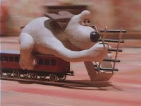 A dog laying down train tracks while riding a train